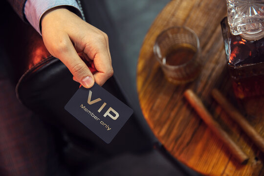 Man holds VIP member card. View from the top on the gentleman's hand that holds exclusive VIP membership card next to the wooden table with whisky in carafe and glass with cigars.