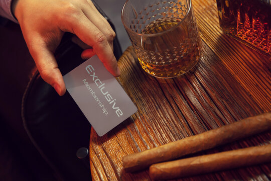 Man's hand puts exclusive membership card on the table. Gentleman's hand puts exclusive membership card on the wooden table with whisky in carafe and glass with cigars.