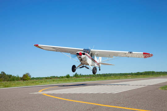 Small white single engine airplane takes off from a municipal airstrip in rural Minnesota