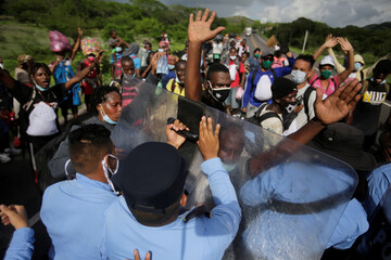 Migrants from Africa, Cuba and Haiti, who are stranded in Honduras after borders were closed due to the coronavirus disease (COVID-19) pandemic, scuffle with police officers while trekking northward in an attempt to reach the U.S., in Choluteca