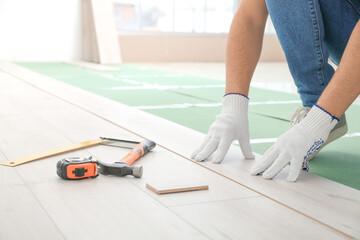 Obraz Carpenter installing laminate flooring in room - fototapety do salonu