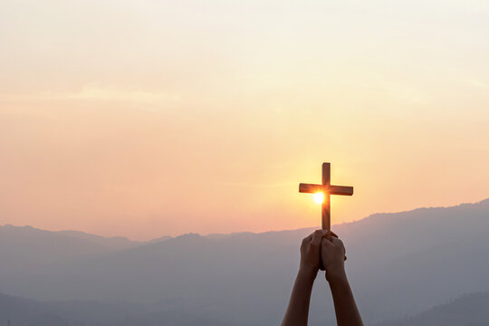 Silhouette human hand holding christian cross for worshipping God at sunset sky background. Christian, Christianity, Religion copy space background.