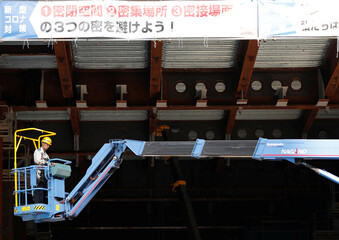 A worker is seen under a banner with safety slogans against the coronavirus disease (COVID-19) at the construction site of an office building in Tokyo