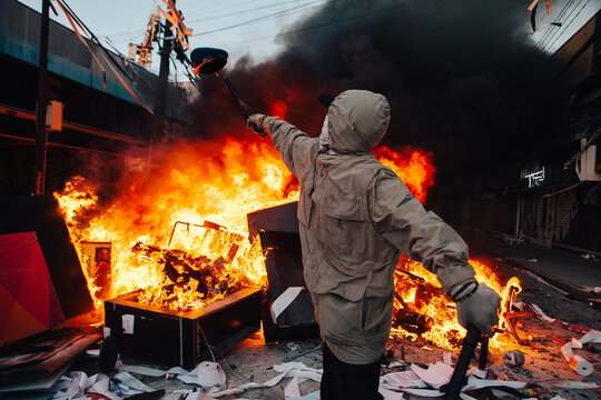 Protester throws on fire guard cap looted from a Bank during the protests