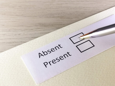 One person is answering question on a piece of paper. The person is thinking to be absent or present.