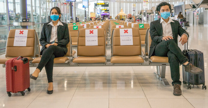 travelers Asian women wearing masks covid 19 disease Prevention An sitting, creating a social distancing while waiting check in with smartphone in the airport terminal