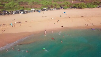 Wall Mural - Tropical beach on Oahu island in Hawaii with car parked along the coastline and people walkin on the beach