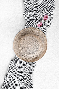 Straw hat, sunglasses and polka dot scarf on concrete background.