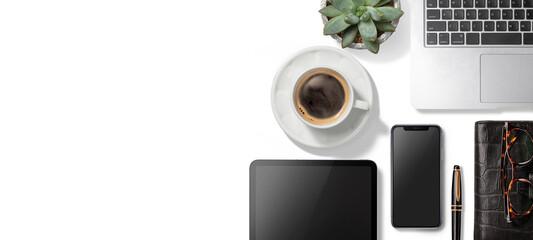 白いテーブルに乗った、ラップトップコンピューター、スマートフォン、タブレット端末、コーヒー、手帳。テレワークのイメージ素材。