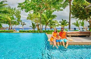 Fototapete - Family of three by poolside. Resort swimming pool at Seychelles.