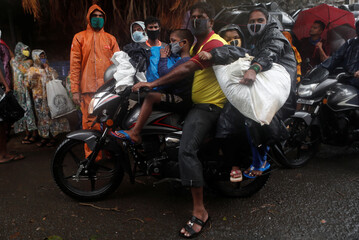 A man rides a bike carrying his family and belongings during an evacuation of a slum off the coast of the Arabian sea as cyclone Nisarga makes its landfall, in Mumbai