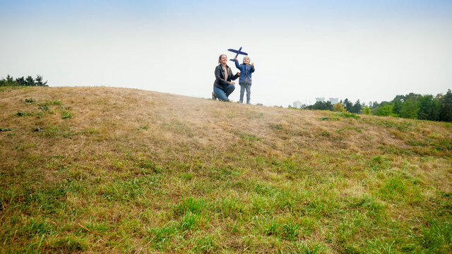 Happy young mother with little son standing on hill top and throwing toy airplane