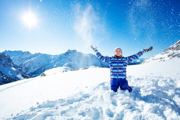 Cute smiling girl throw snow in the air close portrait over blue sky and mountains on sunny day keeping hands up
