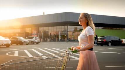 Beautiful smiling blonde girl pushing shopping cart while walking on car parking at shopping mall Fotobehang
