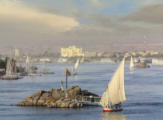 Feluccas on the Nile in the Upper Egyptian city of Aswan. There is a lot of sand in the air after a sandstorm. The evening sun shines and illuminates the river landscape and the city in the background