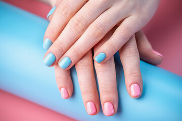 Foto auf Leinwand Maniküre Women's hands with bright summer manicure on a blue and pink background. Trendy glamorous nails in fun colors