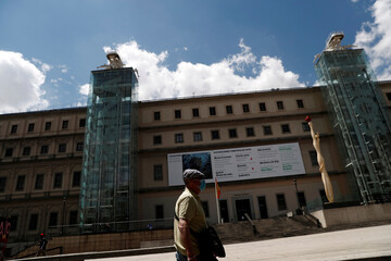 A man wearing a protective mask walks by the Reina Sofia museum as it prepares for reopening on June 6th amid the coronavirus disease (COVID-19) outbreak, in Madrid