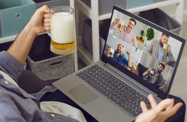 Online video chat friends party. A man with a glass of beer greets friends having a laptop video conference at home.