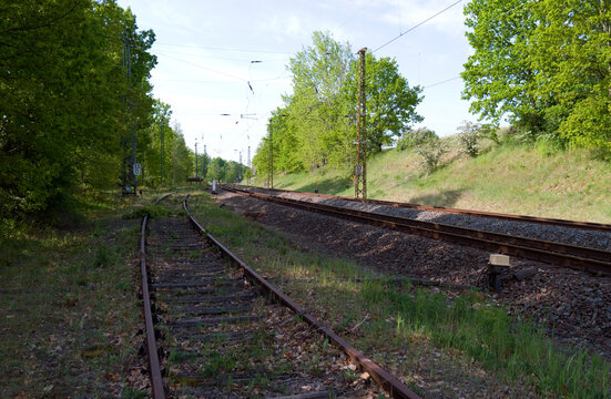 Transportation / Railway: Old and no longer used siding at the edge of an electrified double-track railway line in Central Germany on a sunny day in May