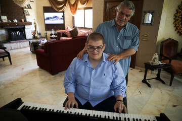 Hamzeh Akroush, who suffers from autism, plays the piano in the presence of his father, Yaser, at their home in the city of Fuhais