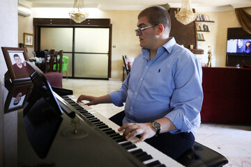 Hamzeh Akroush, who suffers from autism, plays the piano at his home in the city of Fuhais