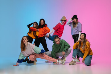 Group of dancers, boys and girls dancing hip-hop in stylish clothes on colorful gradient background...