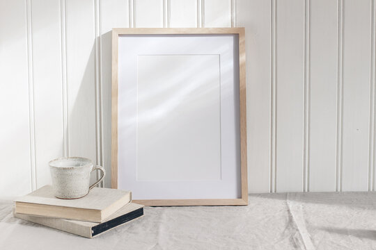 Empty wooden frame mockup on beige linen tablecloth background. White wooden wall paneling background. Artistic still life with cup of coffee and books in sunlight. Scandinavian interior. Art concept.