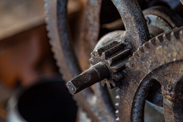 Gears in an old and rusty gear reductor trasmission with soft focus.