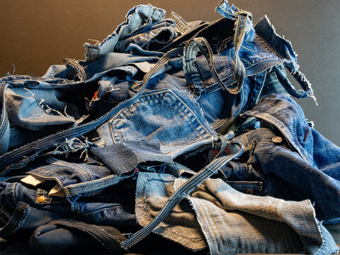 Pile of old blue jeans ready for recycling in the circular economy.  Room for text.