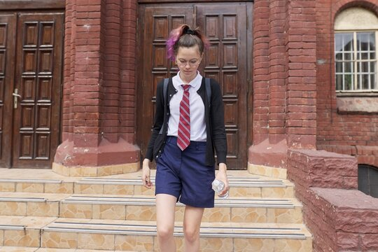 Female student teenager in uniform with backpack, building school background