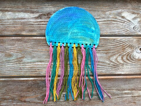 Sea jellyfish made of cardboard and colored yarn, children's crafts.