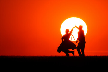 Fototapeten Rot A man and woman in traditional folk costume dancing at a wonderful sunset showing his silhouette