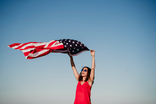young woman holding United States flag outdoors at sunset. Independence day in America, 4th July concept