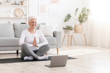 Life Harmony. Relaxed Elderly Lady Practicing Yoga At Home Via Online Tutorials