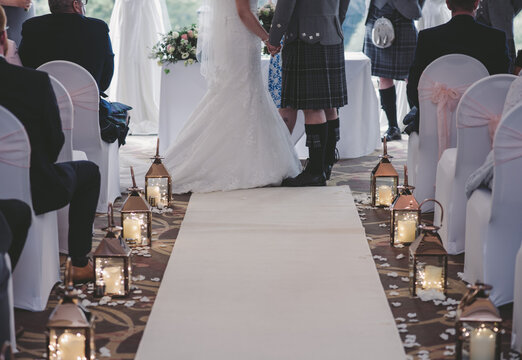 Bride and groom from waist down at top of aisle with candles