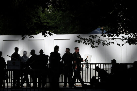 U.S. Secret Service officers are seen silhouetted wearing riot protective equipment outside of the Northwest White House gate during a rally against the death in Minneapolis police custody of George Floyd, near the White House in Washington