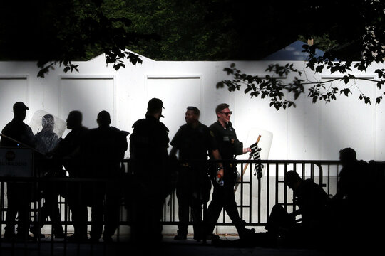 United States Secret Service officers are seen silhouetted wearing riot protective equipment outside of the Northwest White House gate during a rally against the death in Minneapolis police custody of George Floyd, near the White House in Washington