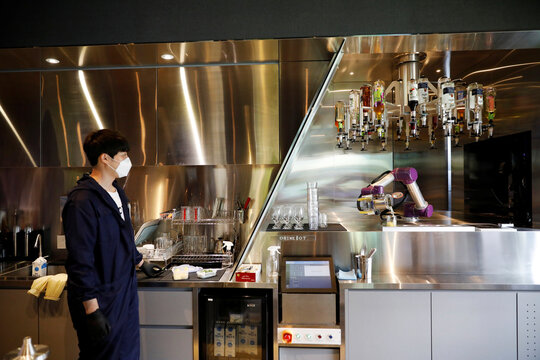 Drink Bot makes a cocktail as an employee wearing a mask to avoid the spread of the coronavirus disease (COVID-19) looks on at a cafe in Seoul