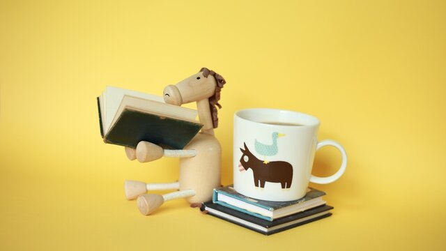 enjoyment of reading books, wooden horse toy, coffee mug with mini books on the yellow background.