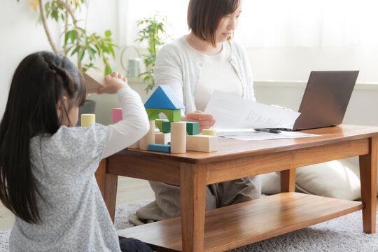 積み木で遊ぶ女の子とテレワークをする母親