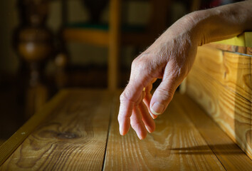 A woman's hand is over a staircase in a room, the background is dark. Concept accident, illness, death