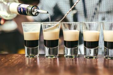 Bartender is preparing array of three layer shots at bar in Vilnius, Lithuania Fotoväggar
