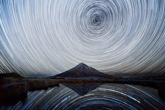 Star trails over Mt. Taranaki reflecting in Pouakai Pool, New Zealand