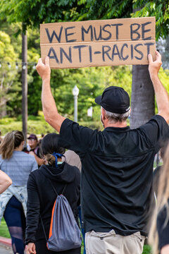 "San Diego, California. June 1st, 2020. ""We must be anti-racist"" sign held by a middle age male during pacific protest claiming justice for George Floyd's murder."