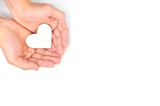 Cupped hands holding a white heart in white background. Charity, pure love, compassion and kindness concept. Top view.