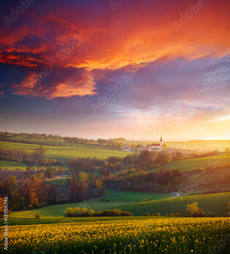 Wall mural Picturesque view on of sunlit wavy fields of agricultural area in morning. Location place of South Moravia region, Czech Republic.