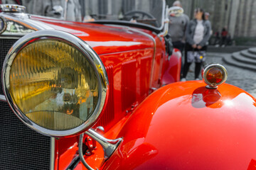 Headlights of a red classic sports car, the Fiat 514 MM as a roadster without hood in Braunschweig, Germany, April 7. 2019