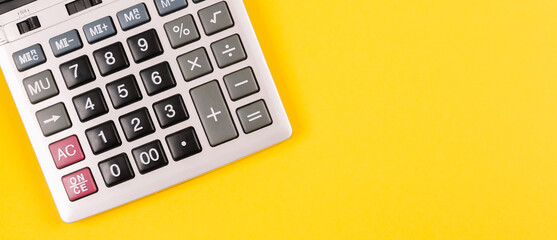 Large silver calculator with gray and black buttons on a yellow background. Conceptual photo of calculations, accounting, computing, profit, loss, tax.