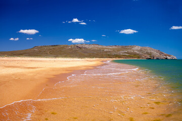 Fototapete - Sandy beach with mountains on the horizon on a sunny summer day