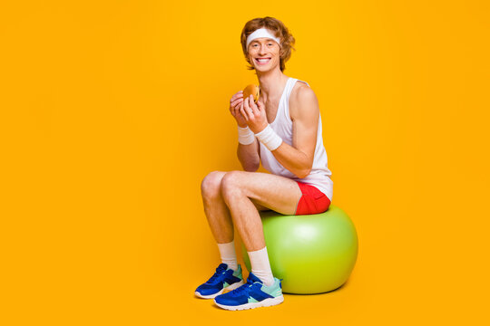 Portrait of his he nice attractive funky cheerful cheery sportive guy sitting on fitball eating forbidden tasty yummy food isolated over bright vivid shine vibrant yellow color background